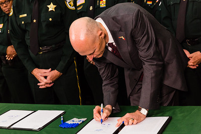 Florida Governor Rick Scott signs the ceremonial bill on victims' rights legislation at the Palm Beach County Sheriff's Office in West Palm Beach on  Monday, April 14, 2016. (Joseph Forzano / The Palm Beach Post)