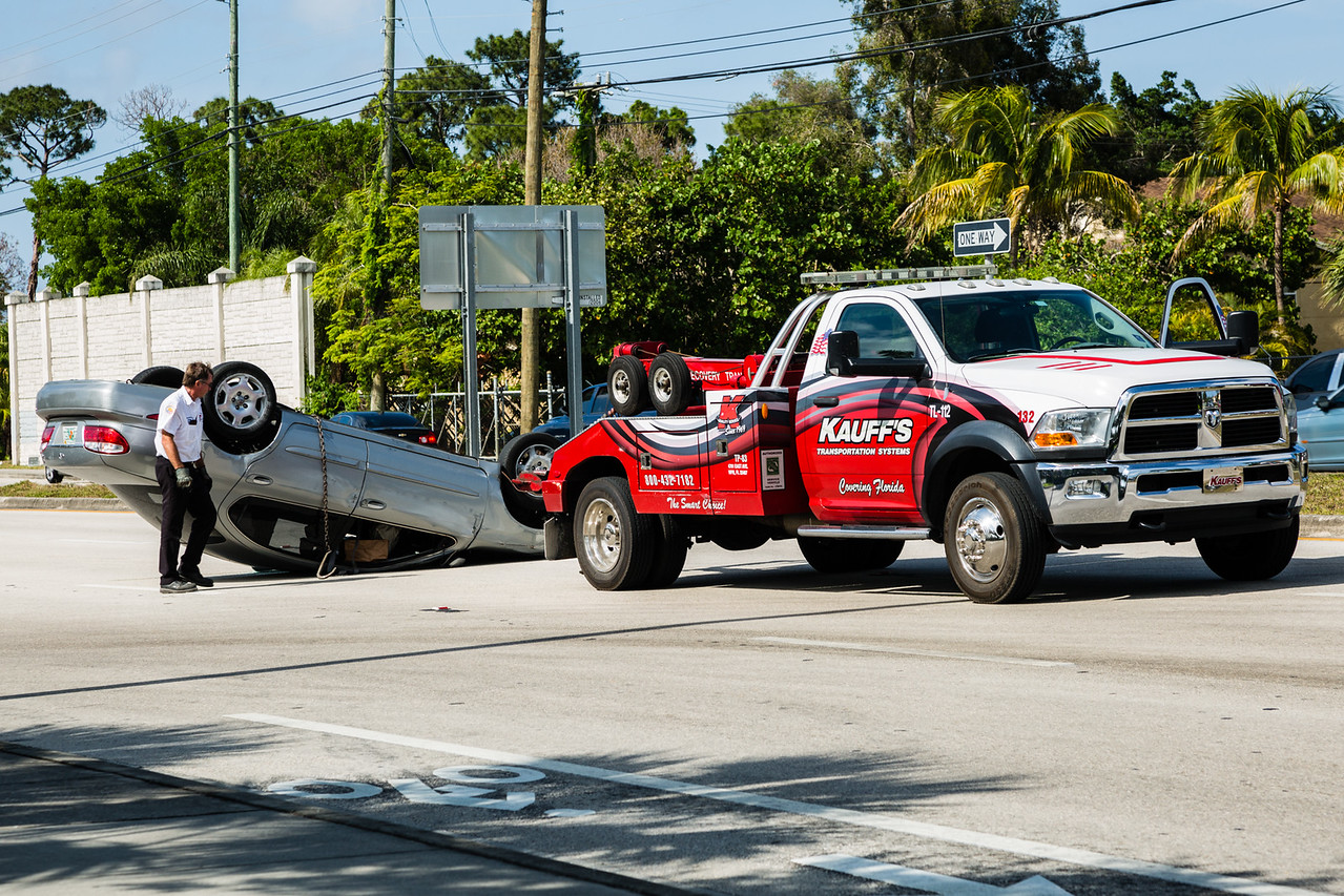 A wrecker prepares to right the overturned car in front of Oxbridge Academy on N. Military Trail in West Palm Beach on Monday, May 5, 2016. (Joseph R. Forzano)