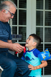 Mariana Lovecchio's son show his new child's smart watch to his grandfather, Javier Valverde Sr. on Sunday, May 22, 2016 in Loxahatchee, FL. Sunday was Mariana's son's 6th birthday and the family celebrated at the sober home where Mariana currently resides. [PER MOTHER, DO NOT TO USE THE CHILD'S NAME IN THE CUTLINE] (Joseph Forzano / The Palm Beach Post)