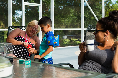 Mariana Lovecchio's son shows sober home mother Kim Kilgore, 60, his new child's smart watch on Sunday, May 22, 2016, while sober home resident Amy Kilgore, 37, looks on. Sunday was Mariana's son's 6th birthday and the family celebrated at the sober home where Mariana currently resides. [PER MOTHER, DO NOT TO USE THE CHILD'S NAME IN THE CUTLINE] (Joseph Forzano / The Palm Beach Post)