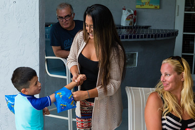 Mariana Lovecchio, 28, helps her son put on  water wings, a present for his 6th birthday on Sunday, May 22, 2016 in Loxhatchee, FL.  Mariana's father Javier Valverde Sr. and sober home resident Erica Piotrowsk, 36, of Loxahatchee, look on.  Sunday was Mariana's son's 6th birthday and the family celebrated at the sober home where Mariana currently resides. [PER MOTHER, DO NOT TO USE THE CHILD'S NAME IN THE CUTLINE] (Joseph Forzano / The Palm Beach Post)