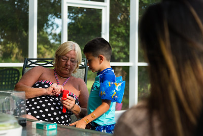 Mariana Lovecchio's son shows sober home  house mother Kim Kilgore, 60, his new child's smart watch on Sunday, May 22, 2016, while Mariana looks on. Sunday was Mariana's son's 6th birthday and the family celebrated at the sober home where Mariana currently resides. [PER MOTHER, DO NOT TO USE THE CHILD'S NAME IN THE CUTLINE] (Joseph Forzano / The Palm Beach Post)