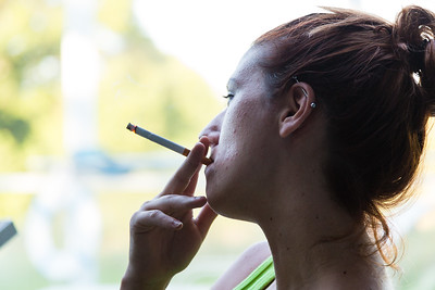 """Shelby Sparrow, 21, from Plantation, Florida smokes a cigarette while she listens to the other residents of the All About Recovery younger women's sober home in Loxahatchee, Florida explain how the morning meditation passage """"Keep it Simple"""" replates to them and their path to recovery on Tuesday, May 31, 2016. Sparrow is a recovering heroin addict and has lived at the sober home for four months. She is 5 months clean. (Joseph Forzano / The Palm Beach Post)"""