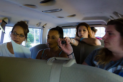 Shelby Sparrow hands her cell phone forward to the front of the van on Tuesday, May 31, 2016. Once the residents arrive at All About Recovery's offices, they are required to hand all of their phones over to the house manager for the duration of their Intensive Outpatient  Program session. (Joseph Forzano / The Palm Beach Post)