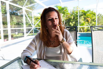 With a cigarette in hand, Shelby Sparrow, 21, of Plantation, Florida, writes in her journal at the All About Recovery younger women's sober home in Loxahatchee, Florida,  on Wednesday, June 21, 2016. Residents of the sober home are encouraged to keep a journal of their experiences, thoughts and feelings as they progress through their addiction recovery. (Joseph Forzano / The Palm Beach Post)