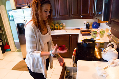Shelby Sparrow, 21, of Plantation, Florida,  gets a measuring cup from a draw while preparing a dinner of pork chops and yellow rice for the residents of All About Recovery's younger women's sober home in Loxahatchee, Florida on Wednesday, June 1, 2016. Sparrow, a recovering heroin addict has been in the sober home since February 2016 and has been clean for five months. (Joseph Forzano / The Palm Beach Post)