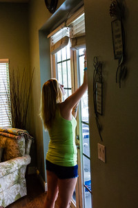 "Shelby Sparrow, 21, of Plantation, Florida, cleans the french doors that lead outside to the patio and pool enclosure at the All About Recovery younger women's sober home in Loxahatchee, Florida on Friday, June 24, 2016. Residents are required to keep the sober home clean, but once a week, the residents  are assigned an area of the sober house to ""deep clean"". (Joseph Forzano / The Palm Beach Post)"