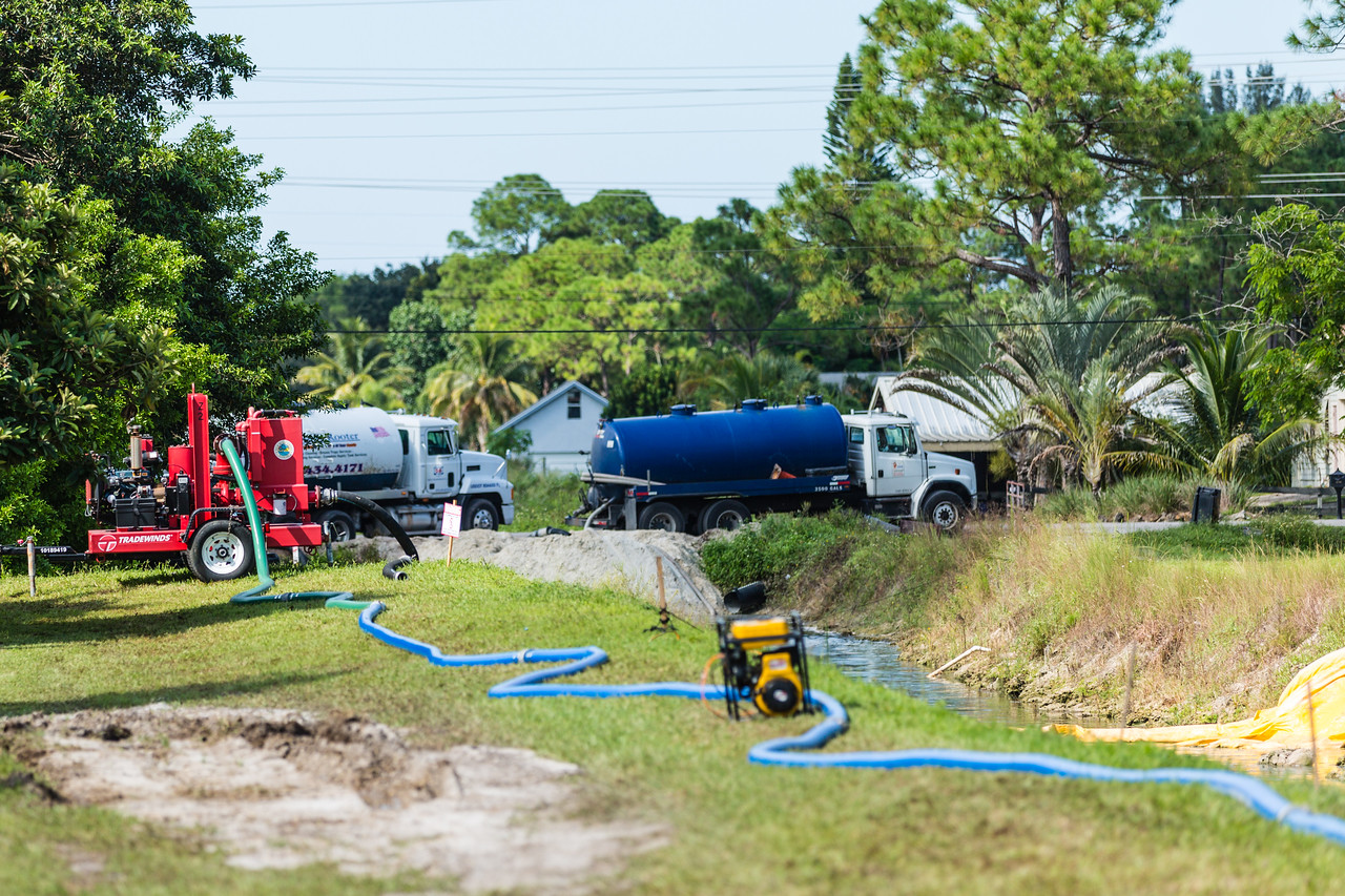 Trucks pump water out of a canal near 110th Avenue North and 41st Court North in The Acreage after a sewage spill. The county has told Acreage residents the water is safe after the spill, but residents are in doubt. (Joseph Forzano / The Palm Beach Post)