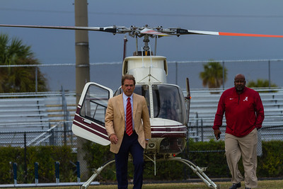 Nick Saban, head coach of the Alabama Crimson Tide and Mike Locksley, assistant Coach make their way off the field after arriving by helicopter at Palm Beach Lakes Community High School on Friday, January 27, 2017. Saban flew in to talk to Rams coaches about potential recruits. (Joseph Forzano / The Palm Beach Post)