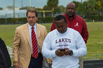 Nick Saban, head coach of the Alabama Crimson Tide and Mike Locksley, assistant Coach are led off the field by Rams coach Al Shipman after arriving by helicopter at Palm Beach Lakes Community High School on Friday, January 27, 2017. Saban flew in to talk to Rams coaches about potential recruits. (Joseph Forzano / The Palm Beach Post)