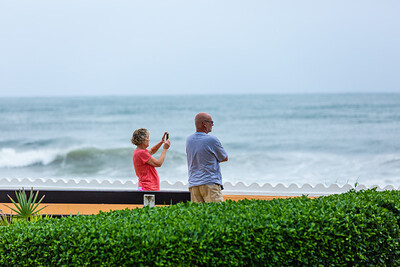 A couple watches the waves break on Palm Beach ahead of Hurricane Dorian side-swiping Florida's east coast on Labor Day, Monday, September 2, 2019. [JOSEPH FORZANO/palmbeachpost.com]