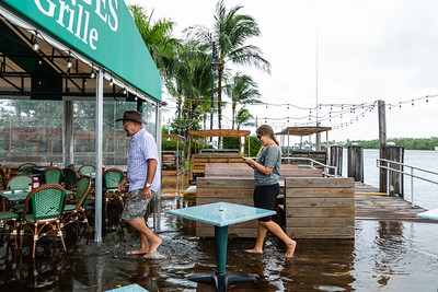 Rick Sabates and Jessica Smith, both of Boynton Beach, walk through the flood waters on the dock outside Two George's in Boynton Beach on Tuesday, September 3, 2019. The flooding is a result of rains from Hurricane Dorian and the King Tide.  [JOSEPH FORZANO/palmbeachpost.com]