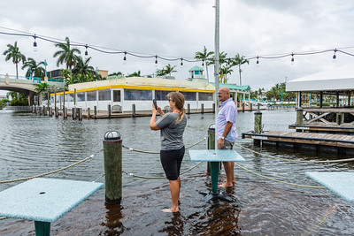 Jessica Smith and Rick Sabates, both of Boynton Beach, takes photos while standing on the flooded dock of Two George's in Boynton Beach on Tuesday, September 3, 2019. The flooding is a result of rains from Hurricane Dorian and the King Tide.  [JOSEPH FORZANO/palmbeachpost.com]
