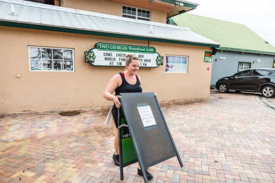 Lindsay Fritz, manager at Two George's, places a sign outside the restaurant to let the public know they will be open on Tuesday, September 3, 2019, as Hurricane Dorian begins to slide up north, just off Florida's east coast. [JOSEPH FORZANO/palmbeachpost.com]