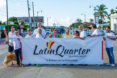 Members of the parade procession stand behind the Latin Quarter banner, ahead of the 1st Annual Latin Quarter WPB 2019 Hispanic Heritage Month Parade, on Saturday, October 5, 2019. [JOSEPH FORZANO/palmbeachpost.com]