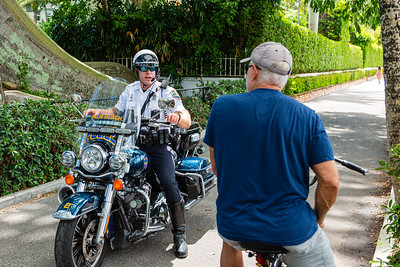 A Palm Beach motorcycle officer stops a bicyclist from entering the Lake Trail due to new restrictions in Palm Beach on Tuesday, March 24, 2020. The Town of Palm Beach put new regulations in place to limit the amount of traffic on the Lake Trail due to COVID-19. [JOSEPH FORZANO/palmbeachdailynews.com]