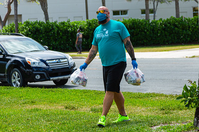Harry Stern, from The Lord's Place, has two bags with food, for the homeless living in Currie Park in West Palm Beach on Tuesday, March 31, 2020. The Lord's Place is still delivering food two days a week during the coronavirus pandemic. [JOSEPH FORZANO/palmbeachpost.com]