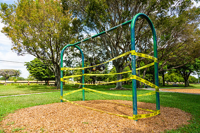 A swing set in Palmetto Park is wrapped in caution tape and the swings are locked together on Tuesday, March 31, 2020. The walking paths in the park are open, but the playground equipment is off-limits due to the coronavirus pandemic. [JOSEPH FORZANO/palmbeachpost.com]