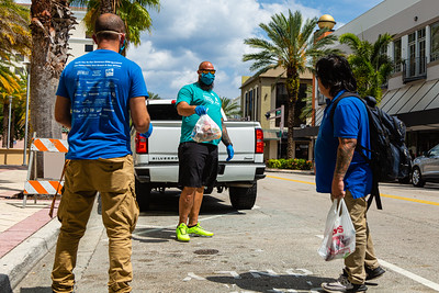 Joey Nieves (left) and Harry Stern (middle) give a bag of food to a homelessman at the Mandel Public Library in downtown West Palm Beach on Tuesday, March 31, 2020. The Lord's Place is still delivering food two days a week during the coronavirus pandemic. [JOSEPH FORZANO/palmbeachpost.com]