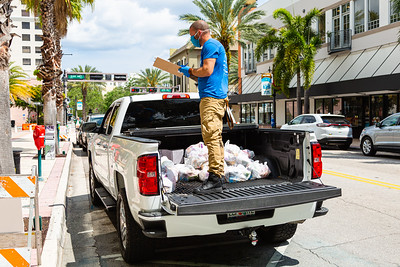 Joey Nieves stands in the bed of a pickup with the bags of food The Lord's Place is giving out at the Mandel Public Libraryin downtown West Palm Beach, on Tuesday March 31, 2020. The Lord's Place is still delivering food two days a week during the coronavirus pandemic. [JOSEPH FORZANO/palmbeachpost.com]