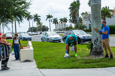 Joey Nieves (right) and Harry Stern (bending) from The Lord's Place, are delivering food parcels to the homeless in Currie Park in West Palm Beach on Tuesday, March 31, 2020. Nieves and Stern wear masks and gloves and make sure they are social distancing. The Lord's Place is still delivering food two days a week during the coronavirus pandemic. [JOSEPH FORZANO/palmbeachpost.com]