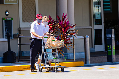 A couple wearing face masks leaves the Publix in Manalapan pushing a small cart with their groceries. [JOSEPH FORZANO/palmbeachpost.com]