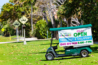 A sign attached to a golf cart lets passersby know that Al Fresco in Palm Beach is open and offering take out and delivery services during the coronavirus pandemic, Thursday, April 2, 2020. [JOSEPH FORZANO/palmbeachpost.com]