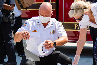 Riviera Beach Interim Fire Chief, John Curd, puts the pieces of the plastic face shield together as Marie Davis, Vice President of SICA looks on. SICA and Amrit combined forces to get PPE for Riviera Beach first responders. [JOSEPH FORZANO/palmbeachpost.com]