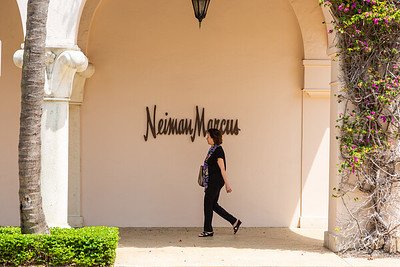 A woman walks past Neiman Marcus on Worth Avenue in Palm Beach, April 21, 2020. Neiman Marcus is expected to file for bankruptcy protection this week. [JOSEPH FORZANO/palmbeachdailynews.com]