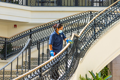 An employee of Berman Property Maintenance wipes down the railing of  the stairs at the Esplanade in Palm Beach, Wednesday, April 22, 2020.  [JOSEPH FORZANO/palmbeachdailynews.com]