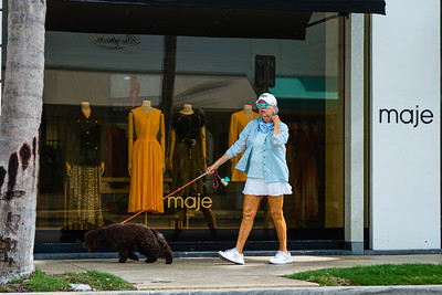A woman walks her dogs past a closed Make on Worth Avenue in Palm Beach, April 23, 2020. All of the retail stores on Worth Avenue are closed due to the coronavirus pandemic. [JOSEPH FORZANO/palmbeachdailynews.com]