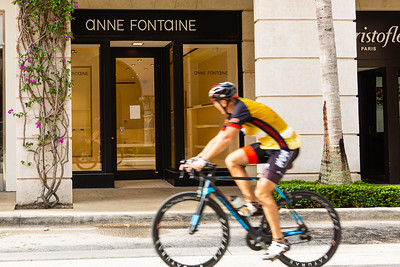 A cyclist rides past an empty Anne Fontaine storefront on Worth Avenue in Palm Beach, April 23, 2020. All of the retail stores on Worth Avenue are closed due to the coronavirus pandemic. [JOSEPH FORZANO/palmbeachdailynews.com]