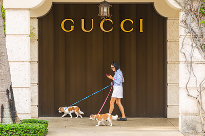 A woman walks her two dogs past the Gucci store on Worth Avenue in Palm Beach, Friday, April 24, 2020. The stores on Worth Avenue have been closed due to the coronavirus pandemic. [JOSEPH FORZANO/palmbeachdailynews.com]
