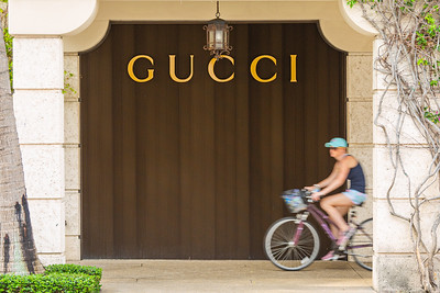 A bicyclist rides up the sidewalk in front of the Gucci store on Worth Avenue in Palm Beach, Friday, April 24, 2020. The stores on Worth Avenue have been closed due to the coronavirus pandemic. [JOSEPH FORZANO/palmbeachdailynews.com]