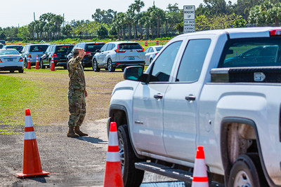 A National Guardsman directs traffic at the entrance to the coronavirus testing sites at the FITTEAM Ballpark of the Palm Beaches, in West Palm Beach, Monday, April 27, 2020. [JOSEPH FORZANO/palmbeachpost.com]