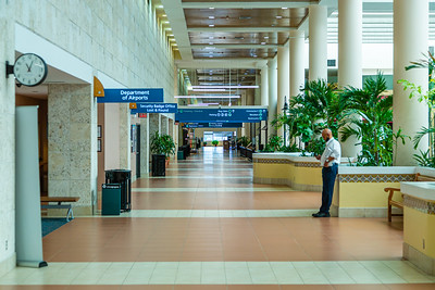 A man checks his smartphone on an otherwise empty concourse at Palm Beach International Airport, Monday, April 27, 2020. [JOSEPH FORZANO/palmbeachpost.com]