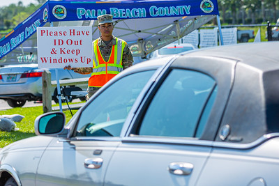 A National Guardsman holds directing drivers to have their identification ready and to keep their windows up at the coronavirus testing sites at the FITTEAM Ballpark of the Palm Beaches, in West Palm Beach, Monday, April 27, 2020. [JOSEPH FORZANO/palmbeachpost.com]