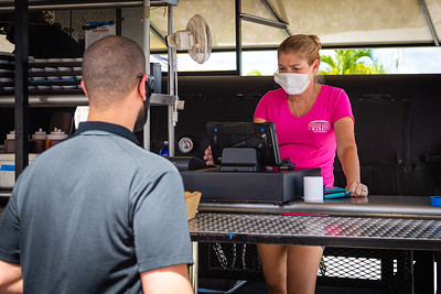 Siobhan Wilson takes a to go order from a customer at the Okeechobee Prime Meat Market roadside BBQ on Wabasso Drive in West Palm Beach, Tuesday, April 28, 2020. [JOSEPH FORZANO/palmbeachpost.com]