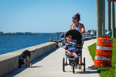 A woman pushes a stroller with her child while walking her dog along S. Flagler Drive in West Palm Beach, Friday, May 1, 2020. [JOSEPH FORZANO/palmbeachpost.com]