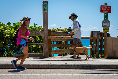 A woman jogs past a man walking his dog in front of Beach Access 51 on Ocean Blvd in Jupiter, Monday, May 4, 2020. [JOSEPH FORZANO/palmbeachpost.com]