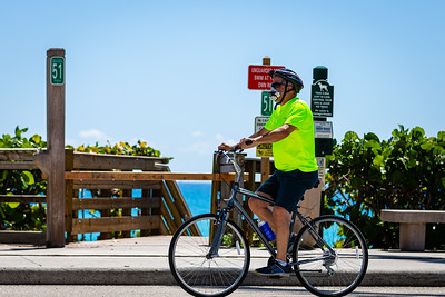 A man with a face mask bicycles north past Beach Access 51 on Ocean Blvd in Jupiter, Monday, May 4, 2020. [JOSEPH FORZANO/palmbeachpost.com]