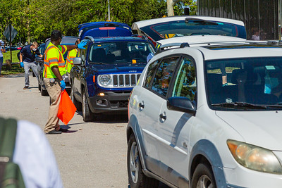 Volunteers direct traffic as other volunteers load food items into the trunks of cars at Dreher Park where the Tree of Life Resource Center  hosted a drive thru community food distribution event in West Palm Beach, Tuesday, May 5, 2020.  The event was sponsored by Schumacher Automotive Group. It was estimated that about 500 cars passed through the site in Dreher Park and about 600 families received food which included produce, meats and diary and  non-perishables food items. [JOSEPH FORZANO/palmbeachpost.com]
