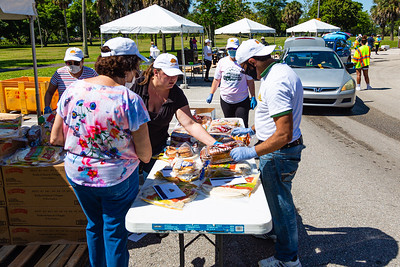 Volunteers sort different breads at Dreher Park where the Tree of Life Resource Center  hosted a drive thru community food distribution event in West Palm Beach, Tuesday, May 5, 2020.  The event was sponsored by Schumacher Automotive Group. It was estimated that about 500 cars passed through the site in Dreher Park and about 600 families received food which included produce, meats and diary and  non-perishables food items. [JOSEPH FORZANO/palmbeachpost.com]