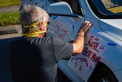 Chuck Bale of Palm Beach Gardens attaches a sign to his car before a special Mother's Day Parade at MorseLife in West Palm Beach, Saturday, May 9, 2020. Residents at MorseLife have been in isolation since the outbreak of the coronavirus. [JOSEPH FORZANO/palmbeachpost.com]