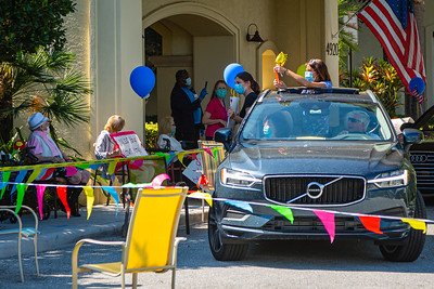 Hallie Kaufman and her mother Joyce Fertig of Palm Beach Gardens hang out of their car with signs for their family member during a special Mother's Day Parade at MorseLife in West Palm Beach, Saturday, May 9, 2020, while Joe Fertig drives with his wife Naomi in the passenger seat. Residents at MorseLife have been in isolation since the outbreak of the coronavirus. [JOSEPH FORZANO/palmbeachpost.com]