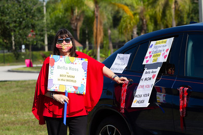 Ginny Nissenbaum of Wellington holds a sign next to her car decorated for her mother Bella Ross who lives at MorseLife in West Palm, Saturday, May 9, 2020. MorseLife held a special Mother's Day parade for residents who have been in isolation since the outbreak of the coronavirus. [JOSEPH FORZANO/palmbeachpost.com]