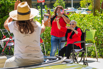 MorseLife resident Sylvia Wolf, seated in a wheelchair, waves as her daughter Pamela Wolf drives by in the special Mother's Day Parade at MorseLife in West Palm Beach, Saturday, May 9, 2020. Residents at MorseLife have been in isolation since the outbreak of the coronavirus. [JOSEPH FORZANO/palmbeachpost.com]