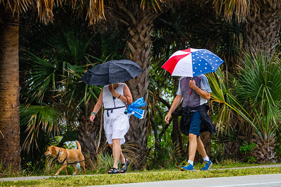A couple hidden under their umbrellas walks their dog in the rain on South Ocean Blvd. in Lake Worth Beach, Sunday, May 10, 2020. A stalled cool front in Central Florida with an area of low pressure over the western Gulf of Mexico is causing the rain over South Florida. [JOSEPH FORZANO/palmbeachpost.com]