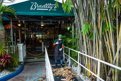 An employee of E.R. Bradley's in West Palm Beach sweeps the bamboo culms from the entrance ramp in, Sunday, May 10, 2020. Bradley's will reopen for sit down business on Monday after Governor Ron DeSantis said restaurants and other businesses can open Monday, May 11, easing coronavirus restrictions in Palm Beach County. [JOSEPH FORZANO/palmbeachpost.com]