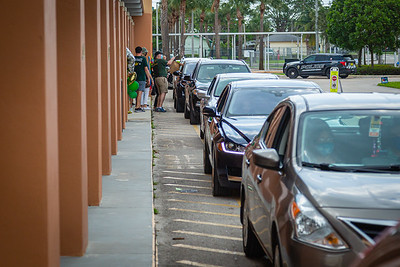 Cars line up along the front of Suncoast High School in Riviera Beach, where students picked up their diplomas along with some graduation gifts and their caps and gowns, Wednesday, May 27, 2020. Suncoast High School gave out caps and gowns and other items along with the prized diplomas in a drive through fashion at the school. [JOSEPH FORZANO/palmbeachpost.com]